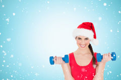 Composite image of festive fit brunette holding dumbbells. Festive fit brunette holding dumbbells against christmas snow falling Royalty Free Stock Image