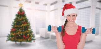 Composite image of festive fit brunette holding dumbbells. Festive fit brunette holding dumbbells against home with christmas tree Stock Image