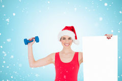Composite image of festive fit brunette holding page and dumbbell. Festive fit brunette holding page and dumbbell against christmas snow falling Stock Photo