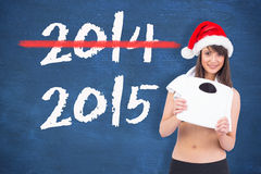 Composite image of festive fit brunette holding a weighing scales Royalty Free Stock Photo