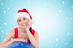 Composite image of festive fit brunette leaning on exercise ball. Festive fit brunette leaning on exercise ball against christmas snow falling Royalty Free Stock Photography