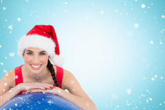 Composite image of festive fit brunette leaning on exercise ball. Festive fit brunette leaning on exercise ball against christmas snow falling Royalty Free Stock Photos