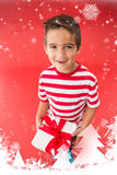 Composite image of festive little boy holding a gift. Festive little boy holding a gift against snow falling Stock Photo