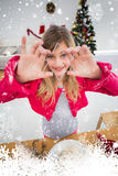 Composite image of festive little girl making christmas cookies Royalty Free Stock Image