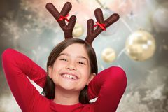 Composite image of festive little girl wearing antlers Royalty Free Stock Images