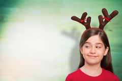 Composite image of festive little girl wearing antlers Stock Photo