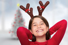 Composite image of festive little girl wearing antlers Royalty Free Stock Photo