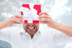 Composite image of festive man holding christmas gift Royalty Free Stock Image