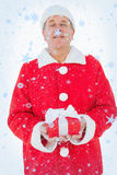 Composite image of festive man holding christmas gift Royalty Free Stock Photo