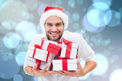 Composite image of festive man holding christmas gifts Royalty Free Stock Image