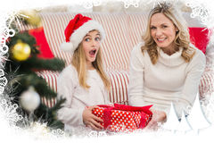 Composite image of festive mother and daughter on the couch with gift Royalty Free Stock Images