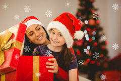 Composite image of festive mother and daughter opening a christmas gift Royalty Free Stock Photo