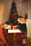 Composite image of festive mother and daughter opening a glowing christmas gift Stock Photo