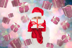 Composite image of festive woman holding gift Stock Photos