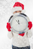 Composite image of festive woman looking at camera holding clock Stock Images