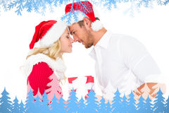 Composite image of festive young couple exchanging presents Royalty Free Stock Photos