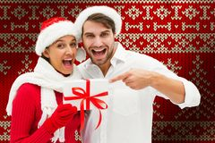 Composite image of festive young couple holding gift. Festive young couple holding gift against red seamless knitted pattern royalty free stock image