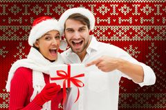 Composite image of festive young couple holding gift stock photography