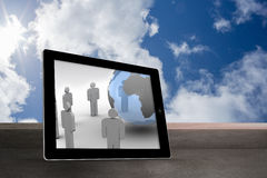 Composite image of figures and earth on tablet screen. Figures and earth on tablet screen against balcony and cloudy sky Royalty Free Stock Image