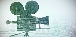 Composite image of film reel camera with tripod. Film reel camera with tripod against high angle view of city by river Stock Image