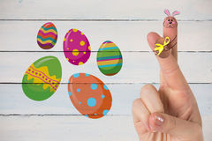 Composite image of fingers as easter bunny. Fingers as easter bunny against painted blue wooden planks royalty free stock photography