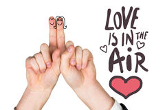 Composite image of fingers crossed like a couple. Fingers crossed like a couple against love is in the air Stock Photo