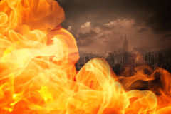 Composite image of fire. Fire against stormy sky over city Royalty Free Stock Image