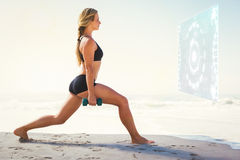 Composite image of fit blonde doing weighted lunges on the beach Royalty Free Stock Photos