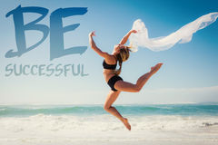 A Composite image of fit blonde jumping gracefully with scarf on the beach Royalty Free Stock Photo