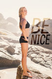 A Composite image of fit blonde standing on the beach on a rock Royalty Free Stock Images