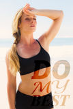 A Composite image of fit blonde wiping her forehead on the beach Royalty Free Stock Images
