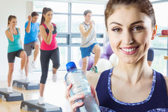 Composite image of fit brunette holding water bottle royalty free stock photos