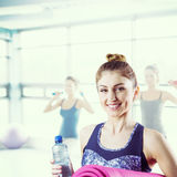 Composite image of fit brunette holding yoga mat Stock Photos