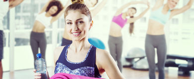 Composite image of fit brunette holding yoga mat Royalty Free Stock Photography