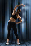Composite image of fit brunette stretching rear view Royalty Free Stock Image