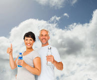 Composite image of fit couple with water bottles gesturing thumbs up Royalty Free Stock Images