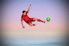 Composite image of fit football player jumping and kicking Royalty Free Stock Image