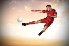 Composite image of fit football player playing and kicking Stock Photo