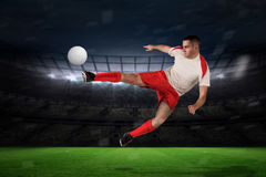 Composite image of fit football player playing and kicking Royalty Free Stock Photo