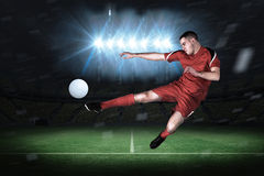Composite image of fit football player playing and kicking Stock Image