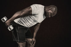 Composite image of fit man exercising with dumbbell Royalty Free Stock Image