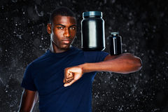 Composite image of fit man holding bottles with supplements on his biceps Royalty Free Stock Photography