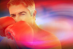 Composite image of fit man punching with boxing gloves Stock Photo