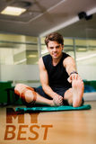 A Composite image of fit man warming up in fitness studio Stock Photos