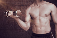 Composite image of fit shirtless man lifting dumbbell Stock Image