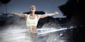 Composite image of fit woman celebrating victory with arms stretched Stock Images