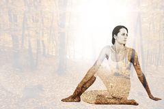 Composite image of fit woman doing the half spinal twist pose in fitness studio Stock Photography