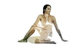 Composite image of fit woman doing the half spinal twist pose in fitness studio Stock Photo