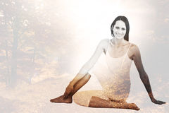 Composite image of fit woman doing the half spinal twist pose in fitness studio Stock Images