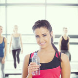 Composite image of fit woman holding water bottle Royalty Free Stock Photos